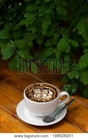 Coffee cup of cappuccino. Hot Cappuccino coffee with zigzag caramel motif or spiderweb art floating on top on wooden background.