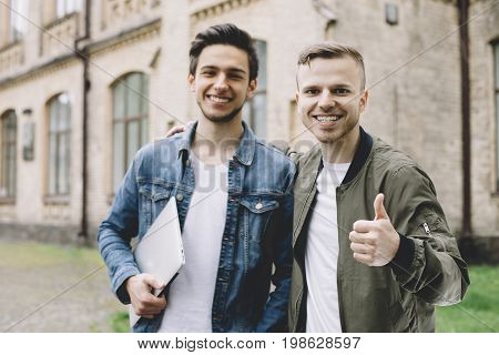 The portrait of two good-looking guys standing outside the building. One of them is holding a laptop in his hand. Another one is having his thumb up which means he is happy and satisfied with something. Both of them are looking and smiling at the camera.