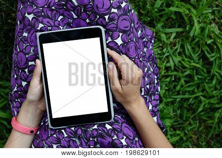 Anonymous woman in purple dress relaxing on green grass with tablet. Rear view. Crop shot with vertical orientation screen template.