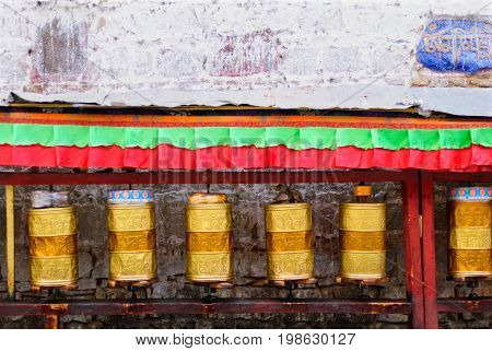 Golden prayer drums row in the street of Lhasa, Tibet background