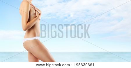 beautiful woman body on sea and sky background protection and skin care concept