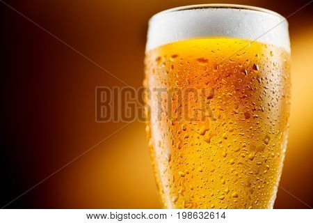 Beer. Cold Craft light Beer in a glass with water drops. Pint of Beer close up on amber color background. Border design