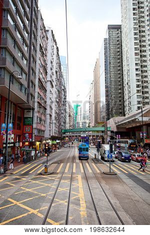 HONG KONG – JULY 18, 2017: Electric trolleys and motor vehicles on a typical downtown street in Hong Kong, China