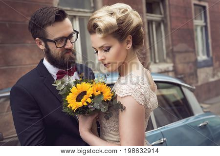 Newlywed couple standing in the street next to an old retro car hugging and embarking on a honeymoon. Focus on the bride