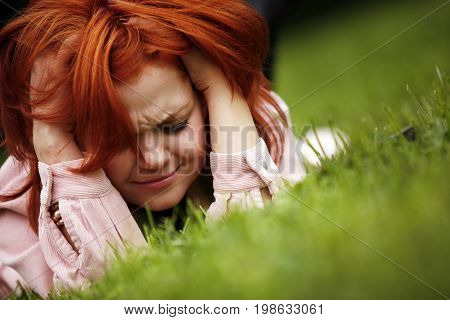 Portrait of the girl with red hair in a grass