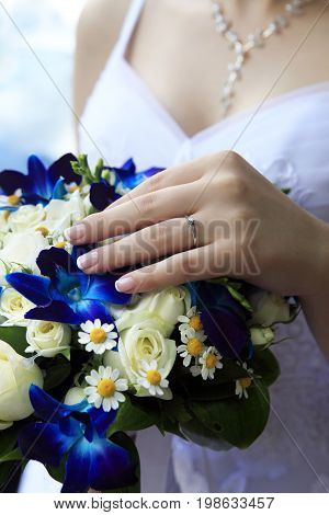 The bride holds a wedding bouquet close up