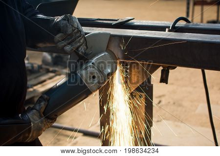 Man Grinding Metal With Angle Grinder