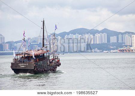HONG KONG – JULY 16, 2017: Traditional wooden sailboat sailing in Victoria harbor