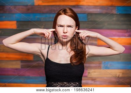 young emotional redhead teenage covering with fingers by her ears. she wearing in green blouse over color wooden background