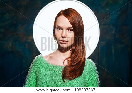 young pretty redhead teenage in greem pullover over dark blue background. beauty model woman with luxurious red hair. hairstyle. holiday makeup