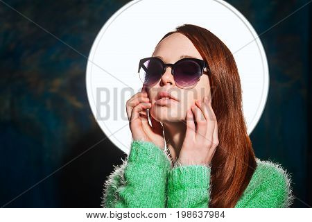young redhead teen in greem pullover and sunglasses over dark blue background. beauty model woman with luxurious red hair. hairstyle.