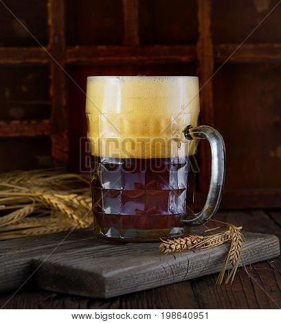Beer in mug on wooden table near brick wall