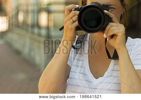 Portrait Of A Photographer Covering Her Face With The Camera.. Photographer Woman Girl Is Holding Ds