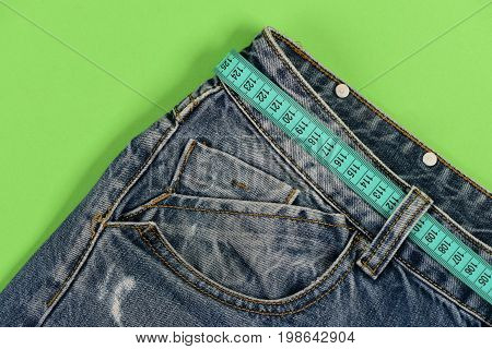 Healthy Lifestyle And Dieting Concept: Jeans With Blue Measure Tape