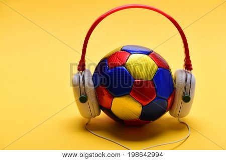 Headset for music placed on ball. Music and sports equipment concept. Headphones in white and red color with colorful soccer ball. Modern earphones and football isolated on warm yellow background