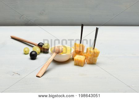 Composition Of Marble Cheese Skewers, Honey And Grapes, Close Up