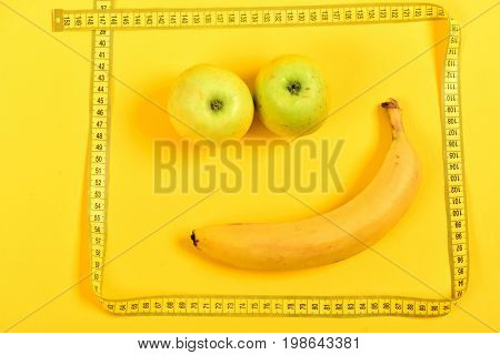Face with smile made of ripe banana and juicy apples framed with tape for measuring on yellow background. Concept of fruit diet