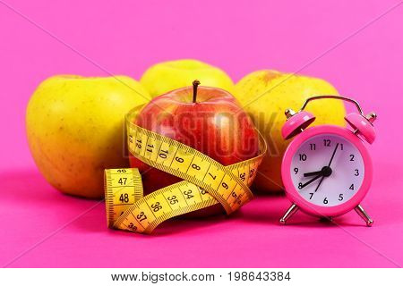 Tape For Measuring Wrapped Around Red Apple Near Yellow Apples