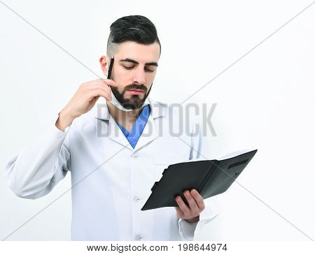 Doctor with beard reads history of present illness in notebook. Treatment and ambulance service concept. Dentist in surgical mask isolated on white background. Man with thinking face in white coat