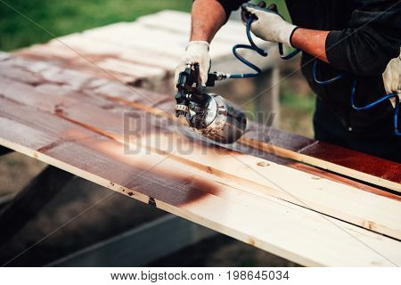 Close-up Details Of Spray Gun And Male Hands Renovating Fence. Woodwork Details With Painter