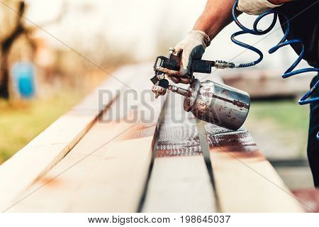 Industrial Handyman, Construction Worker Painting With Spray Gun On Site. Construction Details