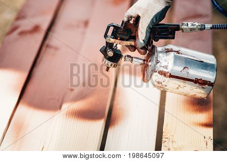 Male Worker Using Spray Gun For Applying Brown Paint Over Timber