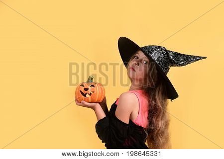 Child In Witch Costume And Jack O Lantern. Halloween Concept