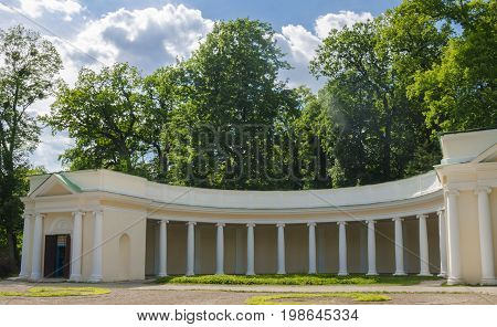 A summer day in a public park is a beautiful colonnade, surrounded by green trees,