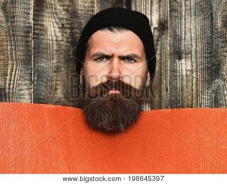 Bearded man long beard. Brutal caucasian serious unshaven hipster in black hat with red paper sheet on grey wooden vintage studio background copy space
