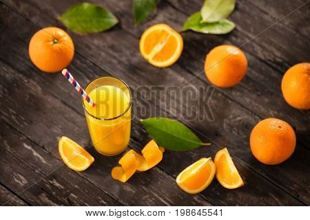 Freshly squeezed orange juice with half oranges on wooden table top view
