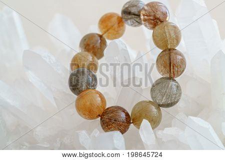 Beautiful translucent assorted colors Rutilated Quartz or Venus' hairstone bead in bracelet on Quartz background