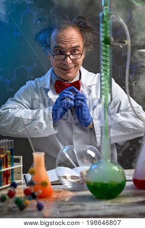 Happy crazy chemist looking in experiment that happens