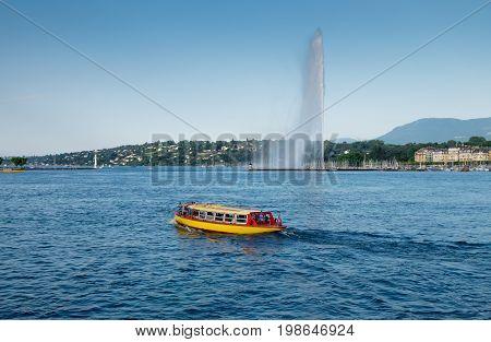 Touristic boat at Geneva Lake on Jet d'Eau fountain background. Sunset time. Switzerland