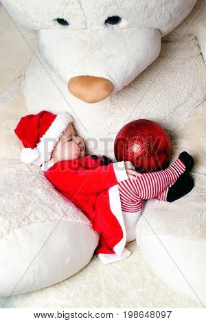Cute little christmas child In the arms of a teddy bear wearing santa claus suit and playing with new years toy