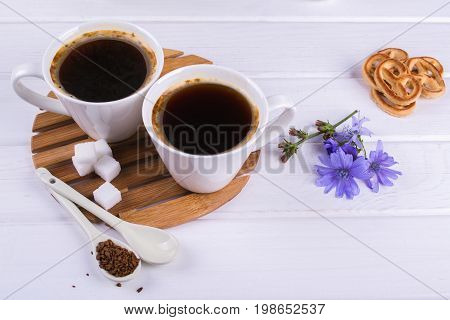 Cup of coffee tea chicory drink hot beverage  with chicory flower and sugar cookies on a white table. Still life with breakfast