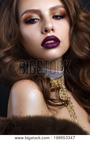 Beautiful young model with evening makeup, perfect skin, wavy long hairstyle in fur cout on black background. Trendy colorful smoky eyes. Purple lips