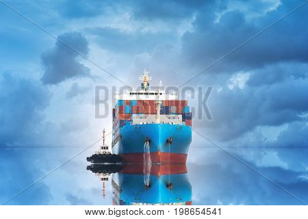 Logistics and transportation of international container cargo ship with port crane bridge in seaport at twilight sky for logistics import export background and transportation industry