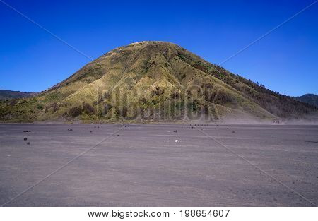 Mount Batok With Green Vegetation The Volcano Next To Mount Bromo Underneath A Clear Blue Sky At The
