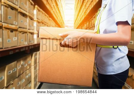 Warehouse worker taking package in the shelf in a large warehouse