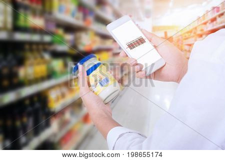 Woman scanning barcode from a label in a supermarket with mobile phone