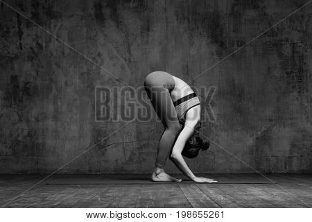 Young beautiful fitness female posing in studio