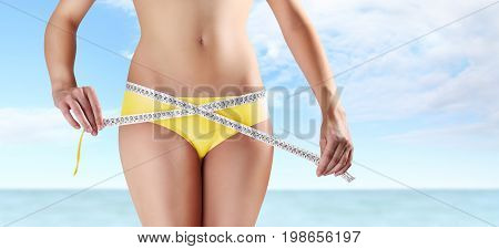 woman holding meter with hands near waistline isolated on blue summer sea and sky background body care diet concept