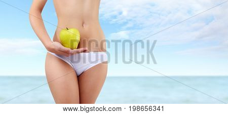 woman holding apple with hand near waistline isolated on blue summer sea and sky background body care diet concept