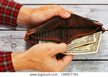 Man in checkered work shirt holding old leather wallet with just two US dollars - paying debt or poverty concept