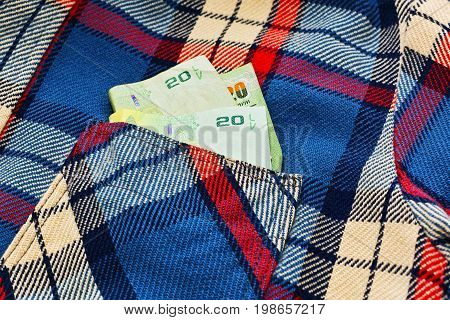 Some Thailand national bank notes - around 11 US dollars - in pocket of old work checkered shirt