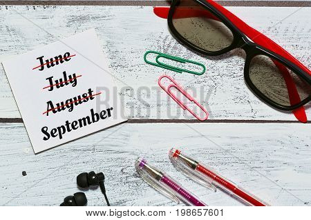 Countdown to autumn concept in loft interior saunglasses earphones office accessories reminder - flat lay top view