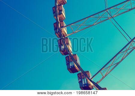 Fragment of Ferris wheel against blue sky, outdoor entertainment fun leisure concept