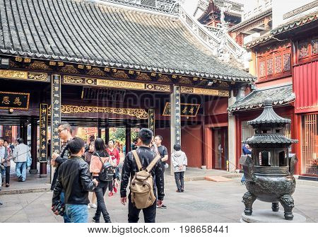 Shanghai, China - Nov 6, 2016: Gate to the 600-year-old Old City God Temple. An ornate incense urn in the courtyard. Visitors frequent this area.