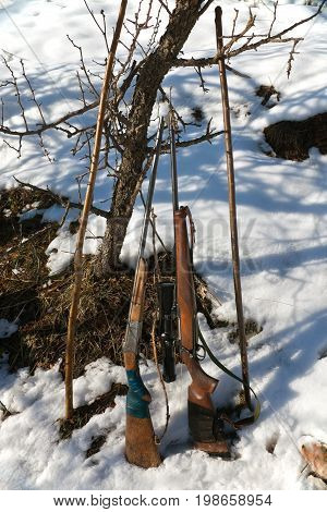 Hunting weapons in the mountains of Tajikistan. The old single-barreled shotgun and modern rifle optics during a hunt for wild boar in the winter.