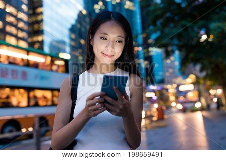 Woman using smart phone in evening